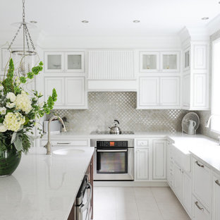 Design ideas for a mid-sized transitional l-shaped eat-in kitchen in Vancouver with a farmhouse sink, recessed-panel cabinets, white cabinets, solid surface benchtops, ceramic splashback, stainless steel appliances, porcelain floors, with island and grey splashback.