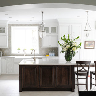 Mid-sized transitional l-shaped open plan kitchen in Vancouver with a farmhouse sink, white cabinets, recessed-panel cabinets, solid surface benchtops, ceramic splashback, stainless steel appliances, porcelain floors, with island and beige splashback.