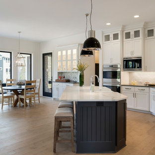 Transitional eat-in kitchen remodeling - Example of a transitional l-shaped light wood floor and beige floor eat-in kitchen design in Minneapolis with a farmhouse sink, shaker cabinets, white cabinets, white backsplash, stainless steel appliances, an island and gray countertops