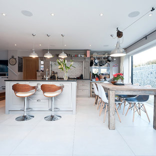 Rural l-shaped kitchen/diner in London with shaker cabinets, grey cabinets, white splashback, metro tiled splashback, stainless steel appliances and an island.