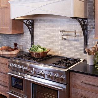 他の地域の巨大なエクレクティックスタイルのおしゃれなキッチン (フラットパネル扉のキャビネット、淡色木目調キャビネット、ソープストーンカウンター、緑のキッチンパネル、磁器タイルのキッチンパネル、シルバーの調理設備の、無垢フローリング) の写真