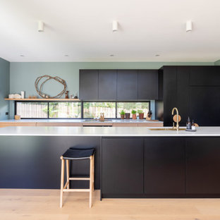Inspiration for a contemporary galley kitchen in Wollongong with an undermount sink, flat-panel cabinets, black cabinets, panelled appliances, light hardwood floors, with island, beige floor and white benchtop.