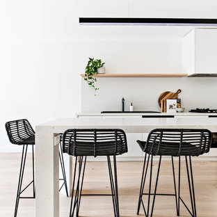Design ideas for a mid-sized contemporary galley eat-in kitchen in Sydney with a drop-in sink, white cabinets, quartz benchtops, white splashback, panelled appliances, with island and white benchtop.
