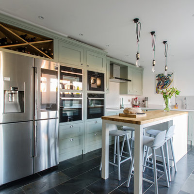 Mid-sized transitional l-shaped kitchen photo in Kent with an undermount sink, recessed-panel cabinets, green cabinets, gray backsplash, stainless steel appliances and an island