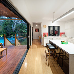 Photo of a large contemporary l-shaped eat-in kitchen in Brisbane with flat-panel cabinets, white cabinets, quartz benchtops, red splashback, ceramic splashback, light hardwood floors, with island, beige floor, white benchtop and a drop-in sink.