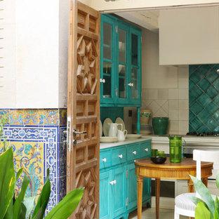 Diseño de cocina en U, mediterránea, pequeña, sin isla, con armarios estilo shaker, puertas de armario azules, salpicadero azul y salpicadero de azulejos de cerámica