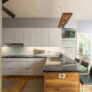 アトランタの中サイズのモダンスタイルのおしゃれなキッチン (アンダーカウンターシンク、フラットパネル扉のキャビネット、グレーのキャビネット、御影石カウンター、白いキッチンパネル、大理石の床、シルバーの調理設備の、淡色無垢フローリング、黄色い床、緑のキッチンカウンター) の写真