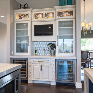 Photo of a mid-sized beach style u-shaped open plan kitchen in Miami with a farmhouse sink, raised-panel cabinets, beige cabinets, marble benchtops, stainless steel appliances and multiple islands.