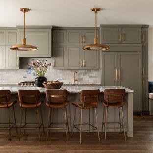 Klassisk inredning av ett vit vitt l-kök, med skåp i shakerstil, gröna skåp, beige stänkskydd, stänkskydd i tunnelbanekakel, integrerade vitvaror, mellanmörkt trägolv, en köksö och brunt golv