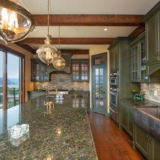 他の地域の大きいおしゃれなキッチン (エプロンフロントシンク、ガラス扉のキャビネット、緑のキャビネット、御影石カウンター、ライムストーンの床、シルバーの調理設備の、無垢フローリング、茶色い床、緑のキッチンカウンター) の写真