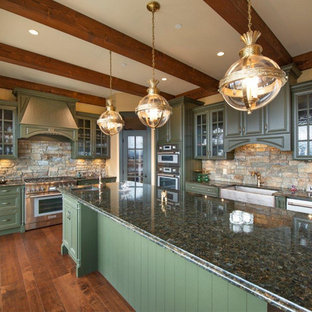 This is an example of a large arts and crafts l-shaped open plan kitchen in Other with a farmhouse sink, glass-front cabinets, green cabinets, granite benchtops, limestone splashback, stainless steel appliances, medium hardwood floors, with island, brown floor and green benchtop.