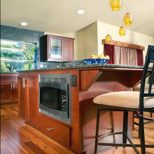 サクラメントの中サイズのシャビーシック調のおしゃれなキッチン (ダブルシンク、レイズドパネル扉のキャビネット、茶色いキャビネット、御影石カウンター、緑のキッチンパネル、石スラブのキッチンパネル、シルバーの調理設備の、無垢フローリング) の写真