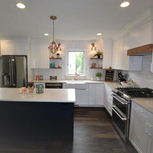 Mittelgroße Shabby-Style Wohnküche in L-Form mit Landhausspüle, Schrankfronten im Shaker-Stil, weißen Schränken, Mineralwerkstoff-Arbeitsplatte, Küchenrückwand in Weiß, Rückwand aus Porzellanfliesen, Küchengeräten aus Edelstahl, Vinylboden, Kücheninsel, braunem Boden und weißer Arbeitsplatte in Nashville