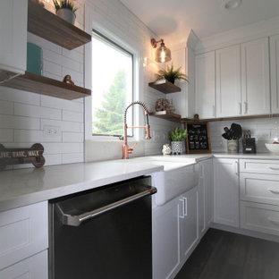 ナッシュビルの中サイズのシャビーシック調のおしゃれなキッチン (エプロンフロントシンク、シェーカースタイル扉のキャビネット、白いキャビネット、人工大理石カウンター、白いキッチンパネル、磁器タイルのキッチンパネル、シルバーの調理設備、クッションフロア、茶色い床、白いキッチンカウンター) の写真