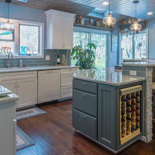 デトロイトの大きいシャビーシック調のおしゃれなキッチン (アンダーカウンターシンク、シェーカースタイル扉のキャビネット、青いキャビネット、クオーツストーンカウンター、青いキッチンパネル、ガラスタイルのキッチンパネル、シルバーの調理設備の、無垢フローリング、茶色い床、グレーのキッチンカウンター) の写真