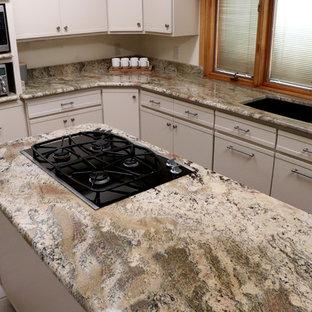 他の地域の広いシャビーシック調のおしゃれなキッチン (アンダーカウンターシンク、フラットパネル扉のキャビネット、白いキャビネット、御影石カウンター、ベージュキッチンパネル、石スラブのキッチンパネル、シルバーの調理設備、セラミックタイルの床、白い床、ベージュのキッチンカウンター) の写真