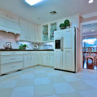 ニューオリンズの大きいおしゃれなキッチン (白いキャビネット、御影石カウンター、白いキッチンパネル、磁器タイルの床、ドロップインシンク、落し込みパネル扉のキャビネット、サブウェイタイルのキッチンパネル、パネルと同色の調理設備、黒い床) の写真