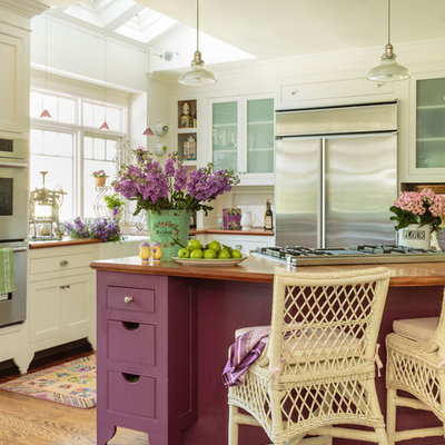 Example of a large cottage chic medium tone wood floor open concept kitchen design in Los Angeles with a farmhouse sink, white cabinets, wood countertops, white backsplash, stainless steel appliances, an island and shaker cabinets