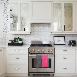 Diseño de cocina comedor en U, romántica, pequeña, sin isla, con armarios con paneles empotrados, puertas de armario blancas, encimera de cuarzo compacto, salpicadero blanco, salpicadero de azulejos de cerámica, electrodomésticos de acero inoxidable y suelo de travertino