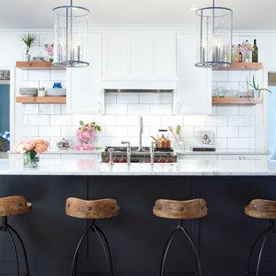 Exemple d'une cuisine parallèle romantique avec un placard à porte shaker, des portes de placard blanches, un plan de travail en marbre, une crédence blanche, une crédence en carrelage métro, un sol en bois brun et un îlot central.