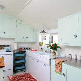 Geschlossene Retro Küche mit flächenbündigen Schrankfronten, Rückwand aus Metrofliesen, integriertem Waschbecken, Edelstahl-Arbeitsplatte, weißen Elektrogeräten, grünen Schränken und Küchenrückwand in Weiß in Sonstige