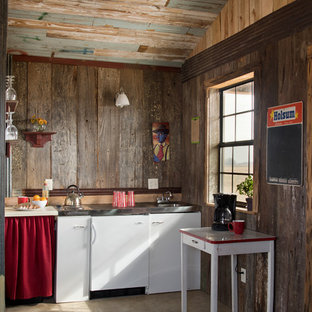 Small rustic kitchen in Jackson with an integrated sink, flat-panel cabinets, white cabinets, stainless steel worktops, concrete flooring and an island.
