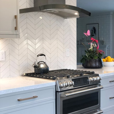 Example of a small transitional galley medium tone wood floor and brown floor open concept kitchen design in San Francisco with an undermount sink, shaker cabinets, quartz countertops, white backsplash, ceramic backsplash, stainless steel appliances, a peninsula, white countertops and gray cabinets