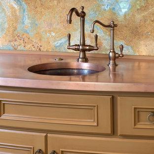Mittelgroße Klassische Wohnküche mit profilierten Schrankfronten, braunen Schränken, Kupfer-Arbeitsplatte, Küchenrückwand in Blau, Rückwand aus Stein, braunem Holzboden und Kücheninsel in Kansas City