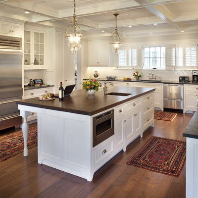 Elegant u-shaped medium tone wood floor and brown floor kitchen photo in Boston with recessed-panel cabinets, stainless steel appliances, soapstone countertops, white cabinets, an undermount sink, white backsplash, subway tile backsplash and an island