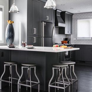 Große Moderne Wohnküche in L-Form mit Schrankfronten im Shaker-Stil, grauen Schränken, Halbinsel, Unterbauwaschbecken, Marmor-Arbeitsplatte, Küchenrückwand in Gelb, Rückwand aus Metrofliesen, Küchengeräten aus Edelstahl und dunklem Holzboden in Calgary
