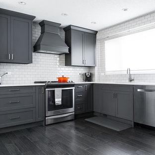 Modern inredning av ett stort kök, med en undermonterad diskho, skåp i shakerstil, grå skåp, marmorbänkskiva, gult stänkskydd, stänkskydd i tunnelbanekakel, rostfria vitvaror, mörkt trägolv, en halv köksö och svart golv