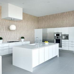 Idéer för mycket stora funkis kök, med en integrerad diskho, luckor med glaspanel, vita skåp, bänkskiva i kvarts, beige stänkskydd, stänkskydd i porslinskakel, rostfria vitvaror, klinkergolv i porslin och flera köksöar