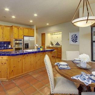 オースティンの中くらいのエクレクティックスタイルのおしゃれなキッチン (ダブルシンク、中間色木目調キャビネット、タイルカウンター、青いキッチンパネル、セラミックタイルのキッチンパネル、シルバーの調理設備、テラコッタタイルの床、青いキッチンカウンター、落し込みパネル扉のキャビネット、赤い床) の写真