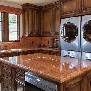 Esempio di una cucina a L mediterranea con lavello sottopiano, ante con bugna sagomata, ante in legno bruno e top arancione