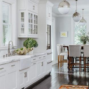 Diseño de cocina comedor clásica, de tamaño medio, con puertas de armario blancas, suelo de madera oscura, suelo marrón, fregadero sobremueble y armarios con paneles empotrados