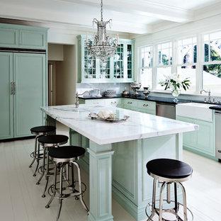 Diseño de cocina clásica, de tamaño medio, con fregadero sobremueble, armarios con paneles empotrados, puertas de armario verdes, encimera de mármol, salpicadero blanco, electrodomésticos con paneles, suelo de madera pintada y una isla