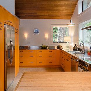 バンクーバーの広いエクレクティックスタイルのおしゃれなキッチン (ドロップインシンク、フラットパネル扉のキャビネット、オレンジのキャビネット、ステンレスカウンター、白いキッチンパネル、シルバーの調理設備、リノリウムの床、アイランドなし) の写真