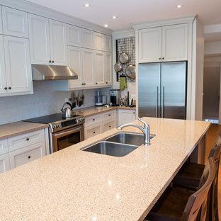 Idéer för att renovera ett stort vintage kök, med en dubbel diskho, luckor med infälld panel, beige skåp, bänkskiva i kalksten, vitt stänkskydd, stänkskydd i sten, rostfria vitvaror, korkgolv och en köksö