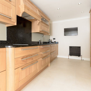 Photo of an expansive traditional galley kitchen in Other with an integrated sink, shaker cabinets, medium wood cabinets, solid surface benchtops, black splashback, panelled appliances and a peninsula.