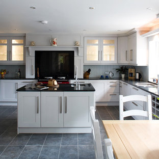 Traditional kitchen/diner in Other with glass-front cabinets, white cabinets, black splashback, glass sheet splashback and coloured appliances.