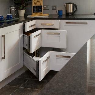 Klassische Küche mit Schrankfronten im Shaker-Stil, weißen Schränken und schwarzer Arbeitsplatte in Sonstige