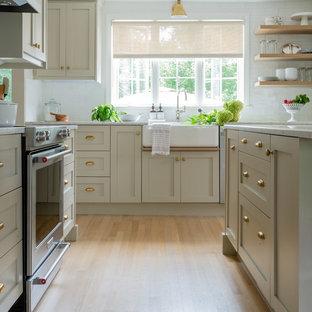 ボストンの中くらいのトランジショナルスタイルのおしゃれなキッチン (エプロンフロントシンク、シェーカースタイル扉のキャビネット、ベージュのキャビネット、大理石カウンター、白いキッチンパネル、サブウェイタイルのキッチンパネル、シルバーの調理設備、淡色無垢フローリング、茶色い床、白いキッチンカウンター) の写真