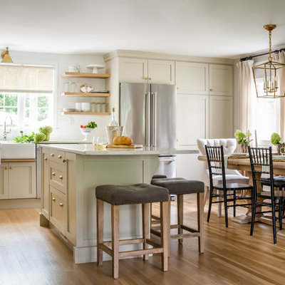 Eat-in kitchen - mid-sized transitional l-shaped brown floor and medium tone wood floor eat-in kitchen idea in Boston with a farmhouse sink, shaker cabinets, beige cabinets, marble countertops, white backsplash, subway tile backsplash, stainless steel appliances, an island and white countertops