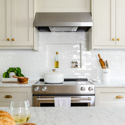 Eat-in kitchen - mid-sized transitional l-shaped light wood floor and brown floor eat-in kitchen idea in Boston with a farmhouse sink, shaker cabinets, beige cabinets, marble countertops, white backsplash, subway tile backsplash, stainless steel appliances, an island and white countertops