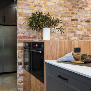 Photo of an expansive industrial galley kitchen pantry in Other with a double-bowl sink, shaker cabinets, grey cabinets, solid surface benchtops, black splashback, subway tile splashback, stainless steel appliances, concrete floors, with island, grey floor and white benchtop.