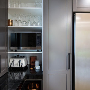 Design ideas for an expansive industrial galley kitchen pantry in Other with a double-bowl sink, shaker cabinets, grey cabinets, solid surface benchtops, black splashback, subway tile splashback, stainless steel appliances, concrete floors, with island, grey floor and white benchtop.