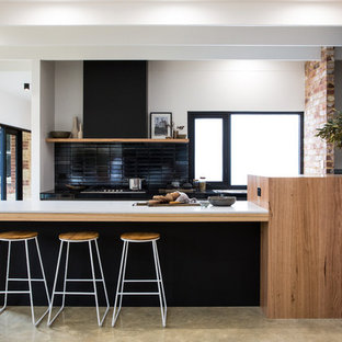Inspiration for an expansive contemporary galley kitchen in Other with solid surface benchtops, black splashback, concrete floors, grey floor, white benchtop, black cabinets and a peninsula.