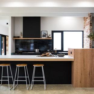 Zweizeilige, Geräumige Moderne Küche mit Mineralwerkstoff-Arbeitsplatte, Küchenrückwand in Schwarz, Betonboden, grauem Boden, weißer Arbeitsplatte, schwarzen Schränken und Halbinsel in Sonstige