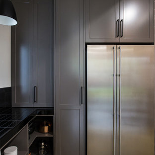 This is an example of an expansive industrial galley kitchen pantry in Other with a double-bowl sink, shaker cabinets, grey cabinets, solid surface benchtops, black splashback, subway tile splashback, stainless steel appliances, concrete floors, with island, grey floor and white benchtop.