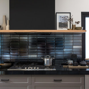 Expansive industrial galley kitchen pantry in Other with a double-bowl sink, shaker cabinets, grey cabinets, solid surface benchtops, black splashback, subway tile splashback, stainless steel appliances, concrete floors, with island, grey floor and white benchtop.